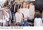 Купить «Woman showing baby costumes on hanger», фото № 29554012, снято 9 октября 2018 г. (c) Яков Филимонов / Фотобанк Лори