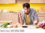 Купить «Young man calculating expences for vegetables in kitchen», фото № 29556560, снято 3 августа 2018 г. (c) Elnur / Фотобанк Лори