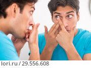 Купить «Man trying contact lenses at home», фото № 29556608, снято 6 августа 2018 г. (c) Elnur / Фотобанк Лори