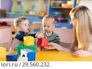 Купить «Cute babies play with blocks. Educational toys for preschool and kindergarten child. Little boys build block toys at playroom or daycare. Education concept.», фото № 29560232, снято 14 декабря 2018 г. (c) Оксана Кузьмина / Фотобанк Лори