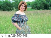 Купить «Beautiful smiling middle-aged woman in nature in summer», фото № 29560948, снято 19 июня 2017 г. (c) Володина Ольга / Фотобанк Лори
