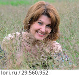 Купить «Portrait of woman in the grass on a summer day», фото № 29560952, снято 19 июня 2017 г. (c) Володина Ольга / Фотобанк Лори