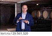 Купить «Winemaker with clipboard in wine cellar», фото № 29561320, снято 22 января 2018 г. (c) Яков Филимонов / Фотобанк Лори