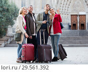 Купить «Two couples with baggage sightseeing and smiling», фото № 29561392, снято 18 января 2019 г. (c) Яков Филимонов / Фотобанк Лори