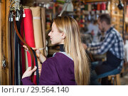Купить «Smiling girl deciding on new belt in leather», фото № 29564140, снято 23 февраля 2019 г. (c) Яков Филимонов / Фотобанк Лори