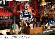 Купить «Adult man worker showing his workplace in leather workshop», фото № 29564148, снято 19 января 2019 г. (c) Яков Филимонов / Фотобанк Лори