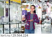 Купить «Woman 19-24 years old in lighter shop is choosing stylish and modern lamp», фото № 29564224, снято 16 февраля 2017 г. (c) Яков Филимонов / Фотобанк Лори
