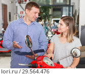 Купить «Couple is shopping and choosing new motobike», фото № 29564476, снято 8 мая 2018 г. (c) Яков Филимонов / Фотобанк Лори