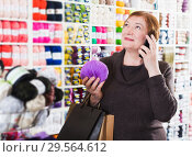 Купить «Woman with shopping bags using phone», фото № 29564612, снято 10 мая 2017 г. (c) Яков Филимонов / Фотобанк Лори