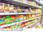 Russia, Samara, November 2018: a variety of packaged products on the shelf in the supermarket. Text in Russian: fructose, chocolate, fount, bitter, roasted, candy. Редакционное фото, фотограф Акиньшин Владимир / Фотобанк Лори