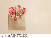 Top view candy canes and red fir tree shaped pins in brown envelope on brown color wood background. Стоковое фото, фотограф Максим Бейков / Фотобанк Лори