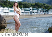 Купить «Young female in swimsuit posing at sea shore near hotel», фото № 29573156, снято 10 июля 2018 г. (c) Яков Филимонов / Фотобанк Лори