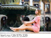 Купить «Sexy woman tourist in dress sitting at stone bench near fountain», фото № 29573220, снято 23 июля 2019 г. (c) Яков Филимонов / Фотобанк Лори