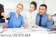 Купить «Female dentist explaining X-ray to patients», фото № 29573424, снято 1 марта 2018 г. (c) Яков Филимонов / Фотобанк Лори