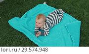 Cute baby lying on towel on lawn. Стоковое видео, видеограф Ekaterina Demidova / Фотобанк Лори