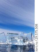 Купить «Transparent chunks of blue ice on a frozen Baikal Lake against a blue sky with stratus clouds. Winter cold background», фото № 29575508, снято 8 марта 2015 г. (c) Виктория Катьянова / Фотобанк Лори