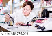 Купить «Pretty female customer looking for make-up items», фото № 29576048, снято 31 января 2017 г. (c) Яков Филимонов / Фотобанк Лори