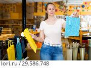 Купить «Woman demonstrates multi colored bags», фото № 29586748, снято 19 апреля 2017 г. (c) Яков Филимонов / Фотобанк Лори