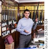 Купить «Salesman showing rifle», фото № 29586924, снято 11 декабря 2017 г. (c) Яков Филимонов / Фотобанк Лори