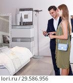 Купить «Couple choosing furniture in shop», фото № 29586956, снято 24 сентября 2018 г. (c) Яков Филимонов / Фотобанк Лори