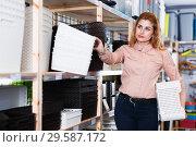 Купить «woman choosing plastic baskets», фото № 29587172, снято 15 января 2018 г. (c) Яков Филимонов / Фотобанк Лори
