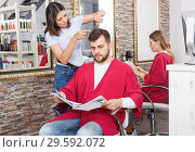 Купить «Smiling young woman hairdresser cuts hair of male client at salon», фото № 29592072, снято 25 апреля 2018 г. (c) Яков Филимонов / Фотобанк Лори