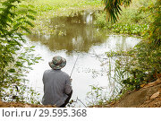 A man with a hat is fishing on a small pond. Стоковое фото, фотограф Михаил Пряхин / Фотобанк Лори