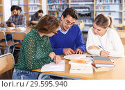 Купить «students sitting in university library, working with professor», фото № 29595940, снято 14 ноября 2018 г. (c) Яков Филимонов / Фотобанк Лори