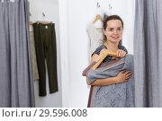 Купить «Woman trying clothes in fitting room», фото № 29596008, снято 10 октября 2018 г. (c) Яков Филимонов / Фотобанк Лори