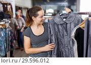 Купить «Woman choosing new overcoat in store», фото № 29596012, снято 10 октября 2018 г. (c) Яков Филимонов / Фотобанк Лори