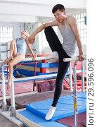 Купить «Man gymnast training gymnastic action at steel bars in gym, woman on background», фото № 29596096, снято 18 июля 2018 г. (c) Яков Филимонов / Фотобанк Лори