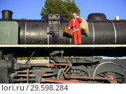 Купить «Man in Santa outfit on old locomotive», фото № 29598284, снято 19 декабря 2017 г. (c) age Fotostock / Фотобанк Лори