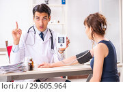 Купить «The young doctor checking woman's blood pressure», фото № 29605964, снято 30 июля 2018 г. (c) Elnur / Фотобанк Лори