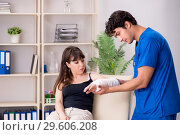 Купить «The young woman with bandaged arm visiting male doctor traumotologist», фото № 29606208, снято 2 июля 2018 г. (c) Elnur / Фотобанк Лори