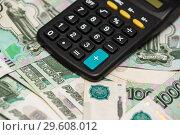 Купить «Карманный калькулятор лежит на тысячных банкнотах», эксклюзивное фото № 29608012, снято 19 декабря 2018 г. (c) Игорь Низов / Фотобанк Лори