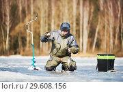 Купить «winter fishing on ice. fisherman or angler hooking the fish», фото № 29608156, снято 17 марта 2018 г. (c) Дмитрий Калиновский / Фотобанк Лори
