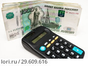 Купить «Калькулятор и пачка тысячных купюр. Фокус на деньгах», эксклюзивное фото № 29609616, снято 19 декабря 2018 г. (c) Игорь Низов / Фотобанк Лори