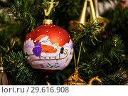 Купить «Новогодний шарик с изображением Деда Мороза на санях висит на ёлке», эксклюзивное фото № 29616908, снято 25 декабря 2018 г. (c) Игорь Низов / Фотобанк Лори