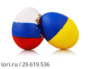 Купить «Blow to Orthodoxy: two Easter eggs painted in the color of the flags of Russia and Ukraine isolated on a white background», фото № 29619536, снято 26 декабря 2018 г. (c) Сергей Чайко / Фотобанк Лори