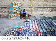 Купить «Craftsman selling traditional uzbek pottery, Bukhara, Uzbekistan.», фото № 29624416, снято 27 января 2020 г. (c) age Fotostock / Фотобанк Лори