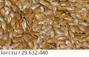 Купить «Pile of flax seeds on rotating table, macro view, healthy food», видеоролик № 29632440, снято 9 июля 2020 г. (c) Dzmitry Astapkovich / Фотобанк Лори