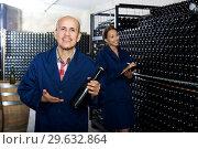 Купить «Man looking at bottle of sparkling wine», фото № 29632864, снято 19 января 2019 г. (c) Яков Филимонов / Фотобанк Лори