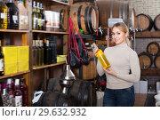 Купить «Young female customer taking bottle of wine», фото № 29632932, снято 16 января 2019 г. (c) Яков Филимонов / Фотобанк Лори