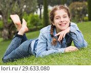 Купить «portrait of smiling young girl while lying in outdoors», фото № 29633080, снято 18 апреля 2017 г. (c) Яков Филимонов / Фотобанк Лори