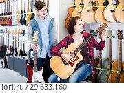 Купить «teenage customers comparing amp and acoustic guitar in guitar shop», фото № 29633160, снято 14 февраля 2017 г. (c) Яков Филимонов / Фотобанк Лори