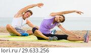 guy and girl practising yoga poses sitting on beach by sea at daytime. Стоковое фото, фотограф Яков Филимонов / Фотобанк Лори