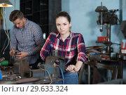 Купить «Portrait of glad female working near vise», фото № 29633324, снято 10 октября 2017 г. (c) Яков Филимонов / Фотобанк Лори
