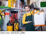 Купить «Guy deciding on best garden sprayer», фото № 29637296, снято 2 марта 2017 г. (c) Яков Филимонов / Фотобанк Лори