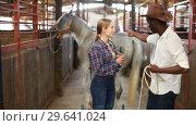 Купить «European girl and afro man who work at stable having emotional discussion», видеоролик № 29641024, снято 13 ноября 2018 г. (c) Яков Филимонов / Фотобанк Лори