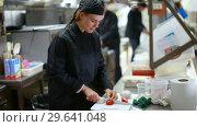 Купить «Cheerful cooks dressed in black uniform at restaurant kitchen», видеоролик № 29641048, снято 13 ноября 2018 г. (c) Яков Филимонов / Фотобанк Лори